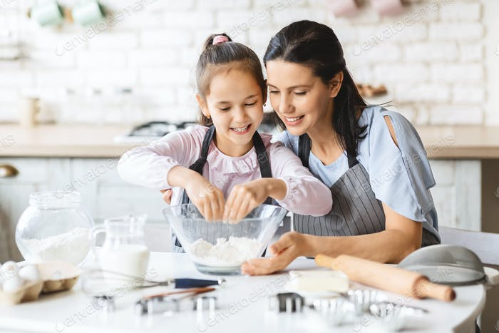 Little girl learning how to cook pastry with mom's help