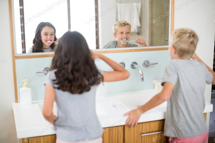 Geschwister putzen ihre Zähne im Bad