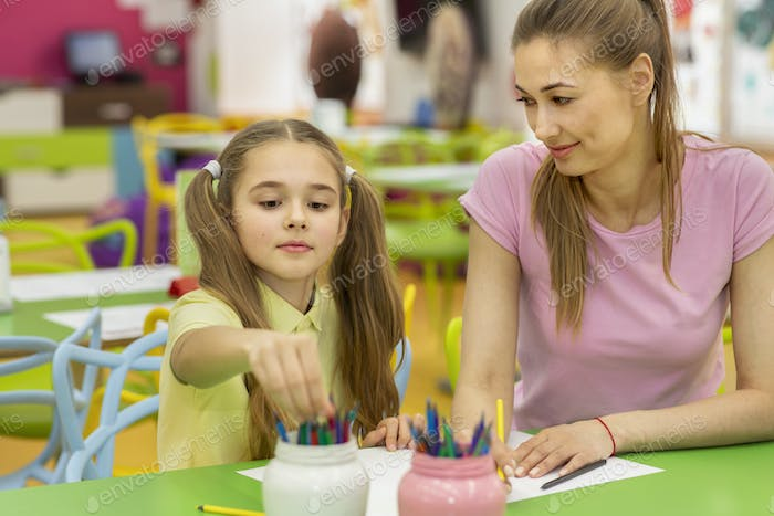 Family leisure activities. Lovely girl and her mom drawing in cafe at indoor kids playground