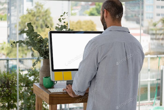 Rear view of designer using computer in office