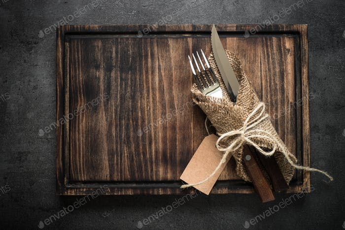 Table setting fork knife and wooden plate.