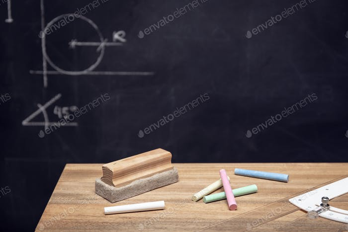 Desk with chalk, eraser and Blackboard with geometry drawings