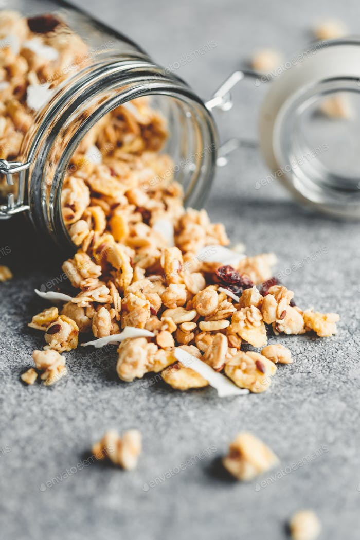 Glass jar of organic granola with berries, cocnut chips and seeds on a blue kitchen table.