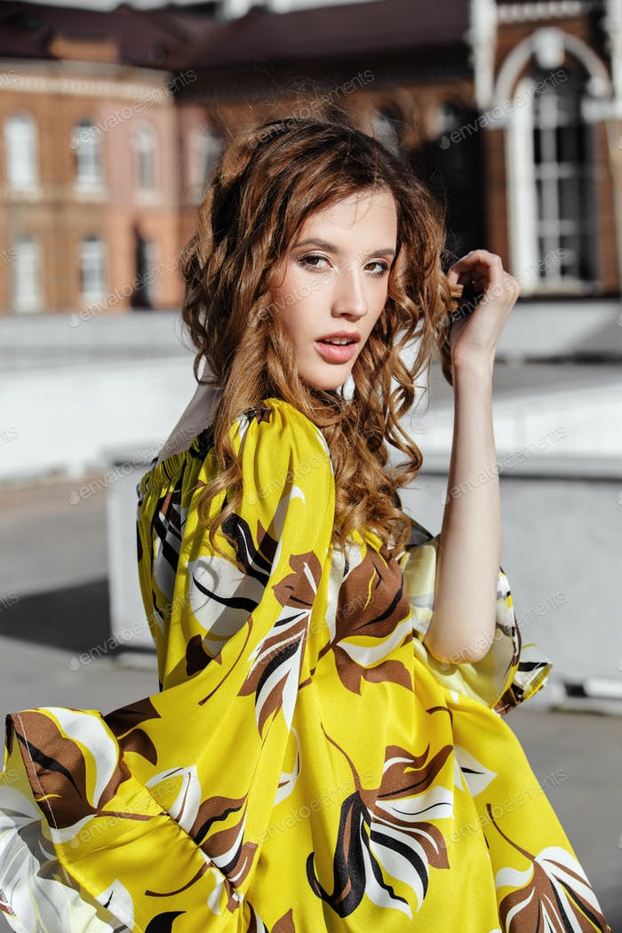 Slim stylish brunette girl dressed in yellow with brown flowers blouse is walking in the street on a