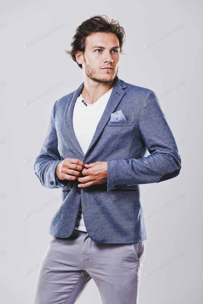 caucasian man wearing blue jacket white shirt and trendy hairsty