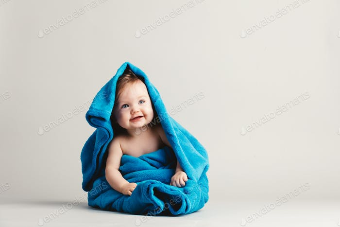 Baby girl covered with a blue warm blanket