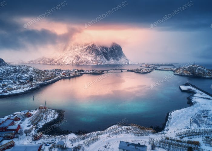 Aerial view of snowy mountain, village on sea coast, colorful sky