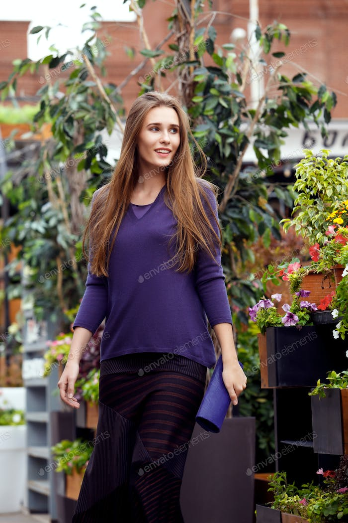 Fashionable girl dressed in a purple sweater and a stylish dark long skirt walks in the park