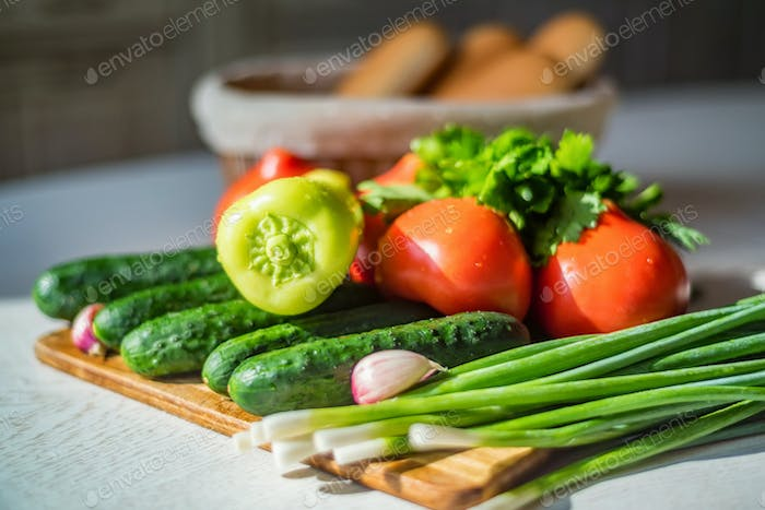 Fresh seasonal vegetables on wooden board on table