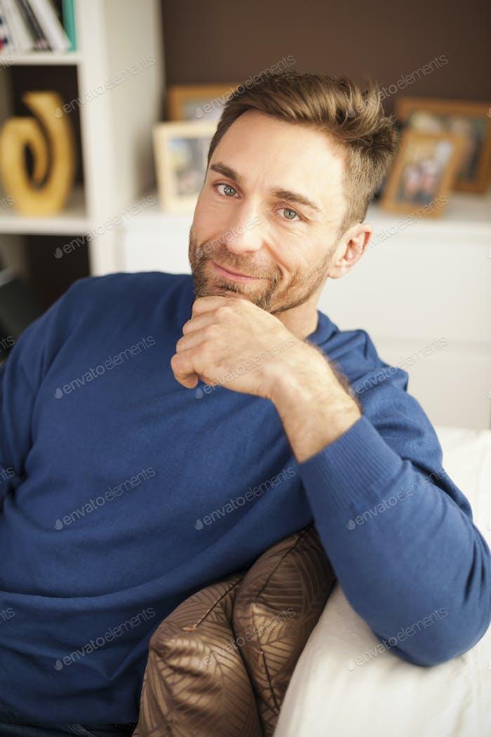 Porträt von gutaussehenden Mann sitzt auf Sofa
