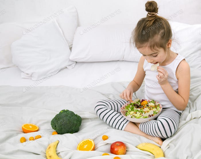 Cute little girl with fruits and vegetables.