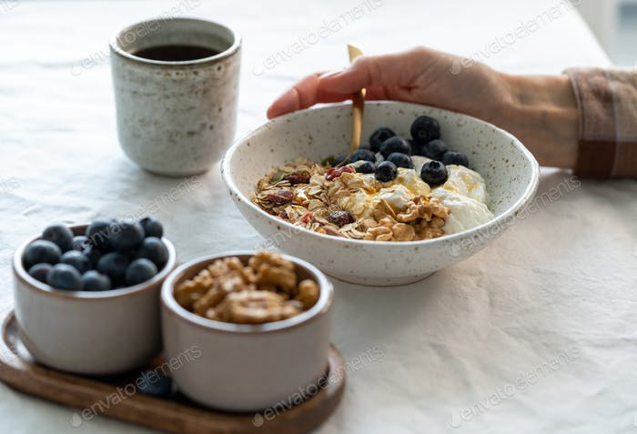 Eating healthy lifestyle breakfast with granola muesli and yogurt in bowl on white table