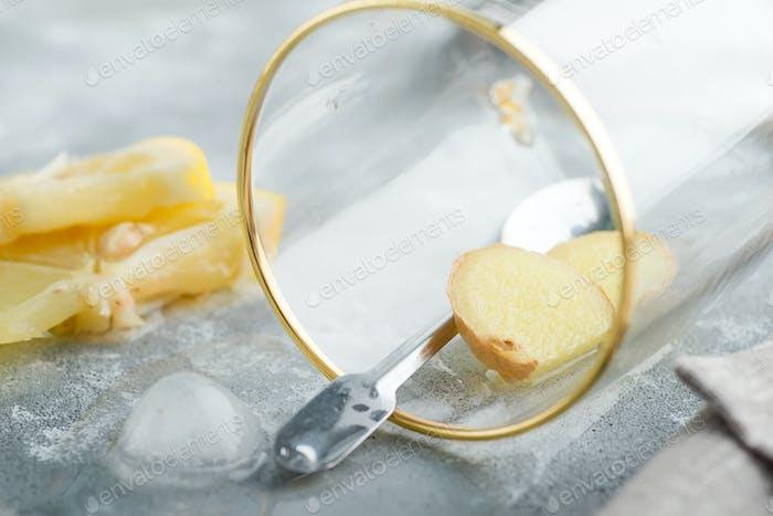 Erfrischender Ingwer in einem Glas mit Tropfen Wasser auf einem marmorgrauen Tisch