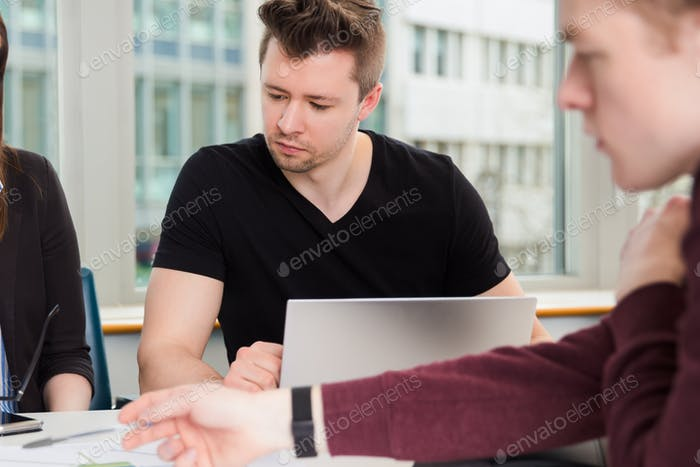 Businessman With Laptop And Colleagues Sitting At Desk