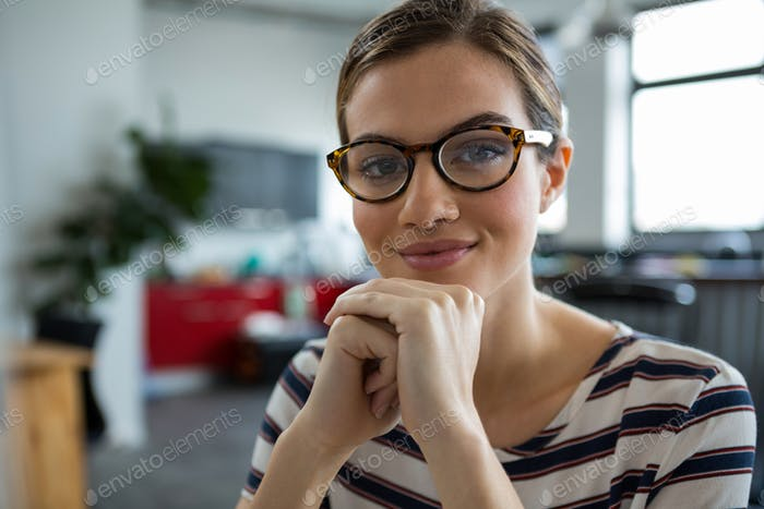 Smiling female graphic designer in spectacles at creative office