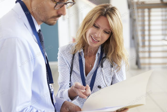 Young male and female doctors consulting notes at meeting