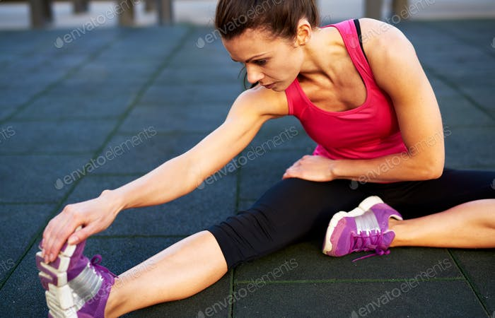 Woman on floor stretching her leg.