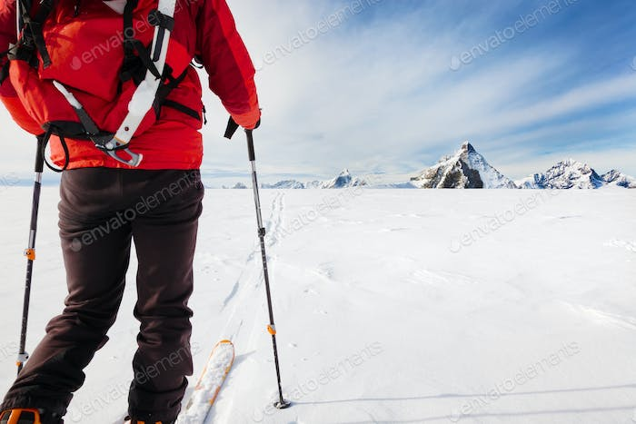 Mountaineer exploring a glacier with the skis