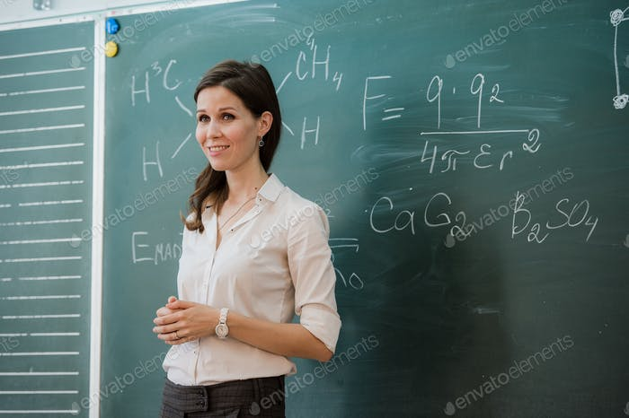 Young happy female teacher with arms crossed standing against green board