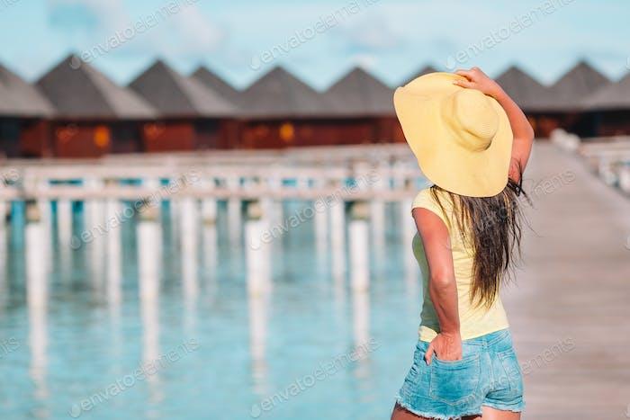 Frau mit gelbem Hut entspannen am Schwimmbad im exotischen Resort