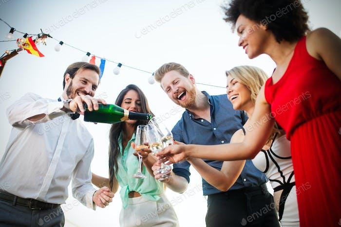 Gruppe von glücklichen Freunden Party und Toasten Getränke