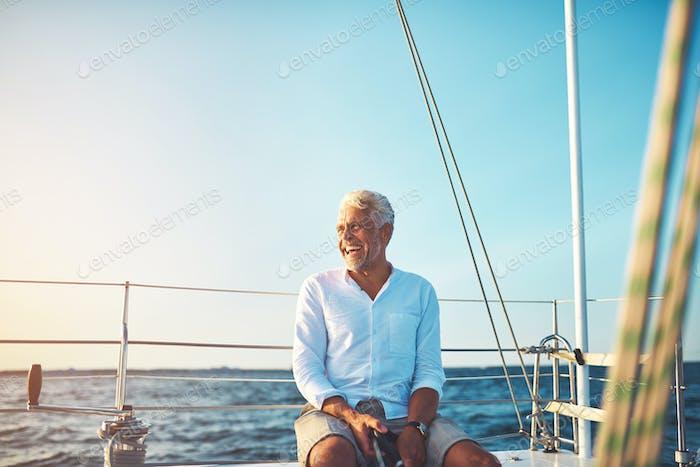 Mature man enjoying a sunny day sailing on the ocean