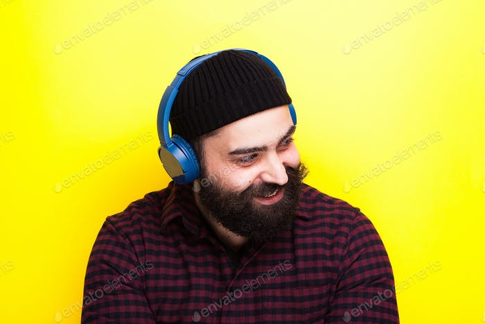 Hipster with a blue wireless headset listening to music