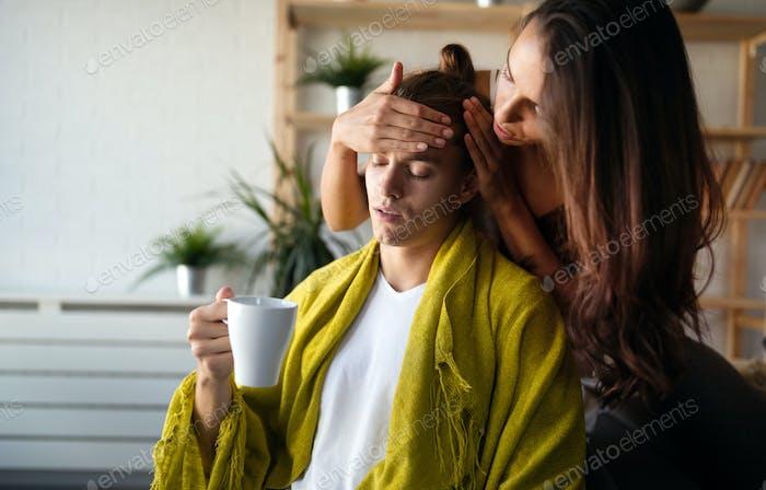 Besorgte Frau Wangen Temperatur des Mannes zu Hause. Fieber, Grippe, Krankheit, Menschenkonzept