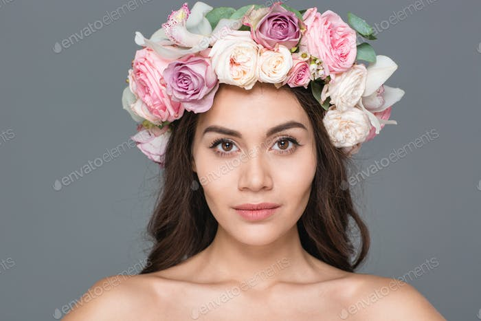 Charming woman with wreath of roses looking at camera