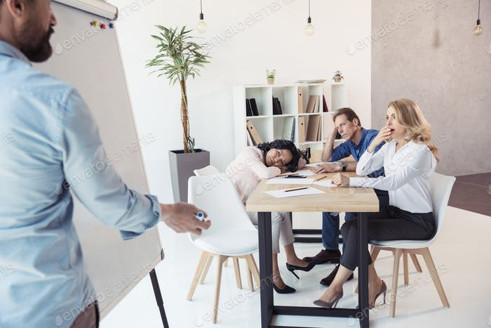 businessman writing on whiteboard while his tired colleagues sitting at table at meeting
