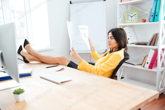 Businesswoman reading report papers in office