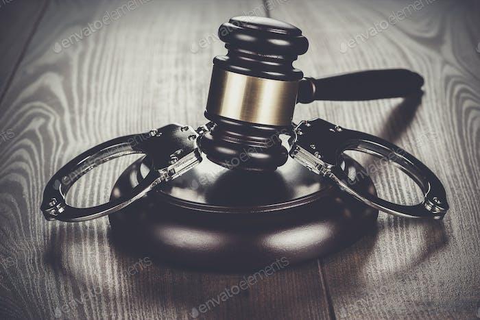 Handschellen und Richter Hammer auf braunem Tisch