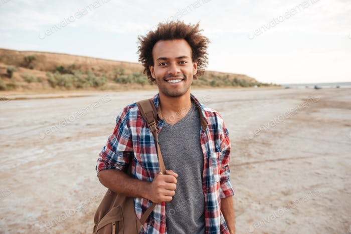 Cheerful african man standing outdoors and holding backpack