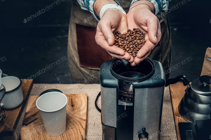 Close up image of a man putting coffee beans into a coffee machi