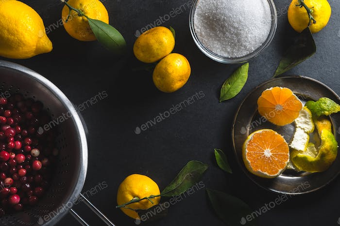 Frame of tangerines, lemon and cranberries on a gray table