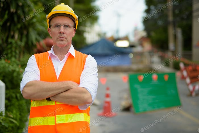 Mature man construction worker at the construction site in the c