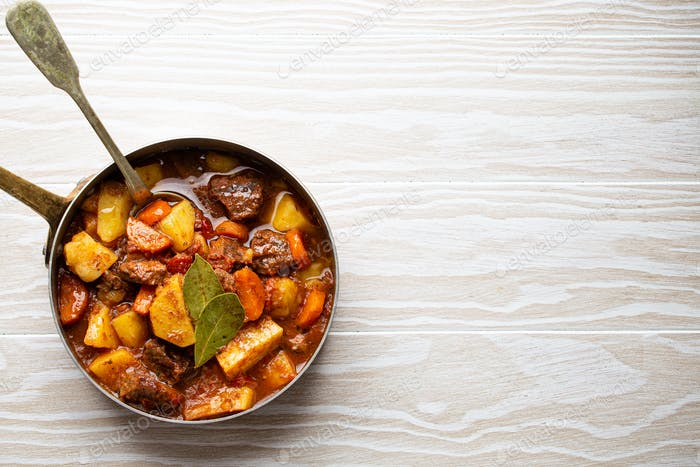 Delicious stew with meat, potatoes, carrot and gravy in rustic copper pot