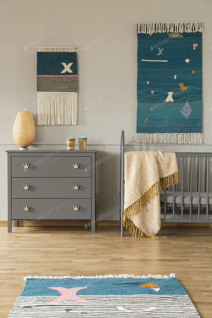 Decor on the wall above grey cabinet and child's bed with blanke