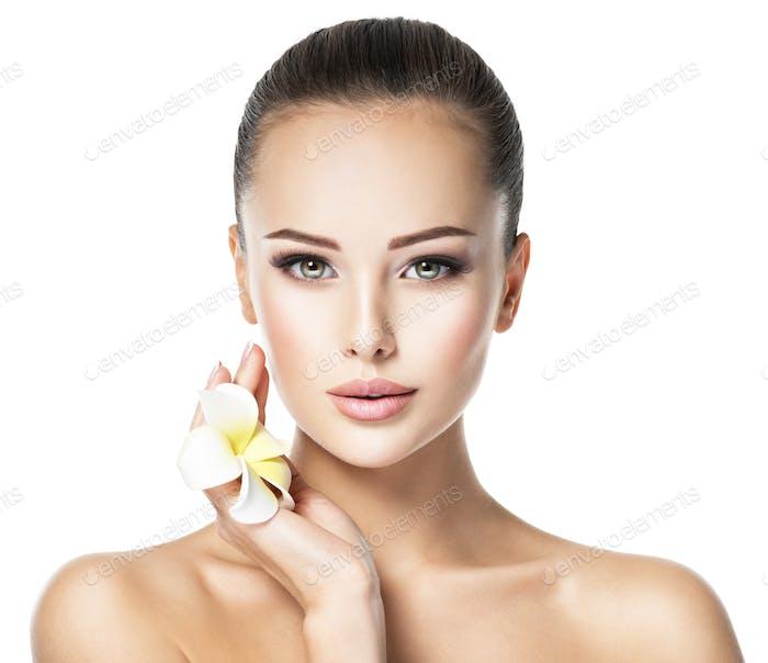 Schönes Gesicht der jungen Frau mit Blume
