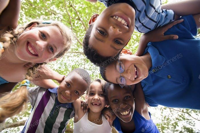 Los niños abrazando en círculo alrededor de la cámara y sonriendo