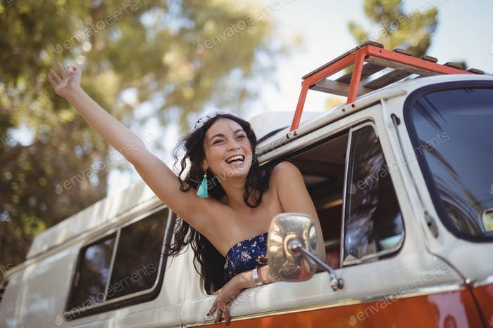 Haooy woman leaning on window of motor home