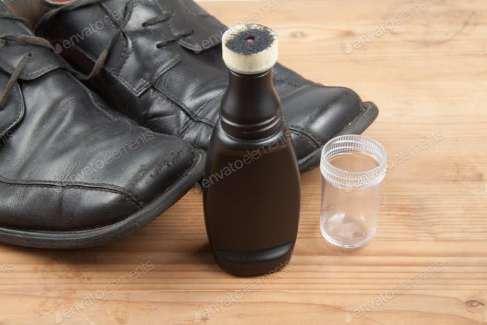 Convenient liquid shoe polish with worn out shoes on wooden plat