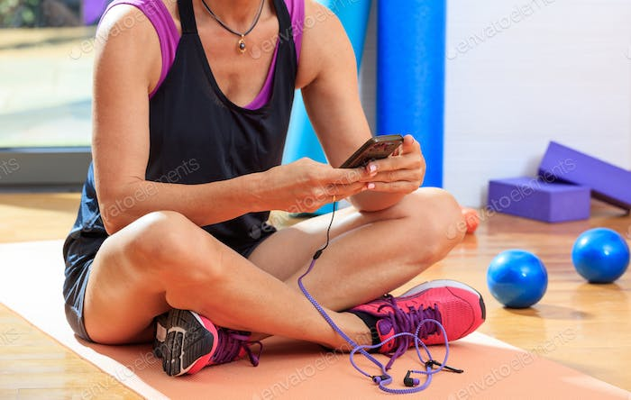 Woman holding a smartphone in a fitness class