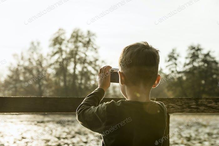 Junge fotografiert Natur mit einer Kompaktkamera