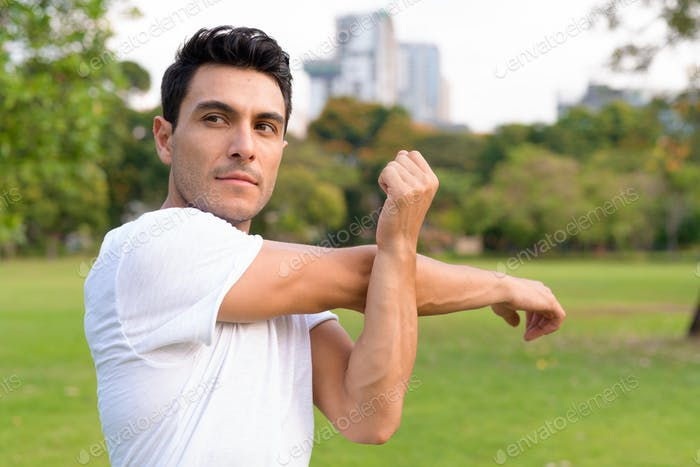 Young handsome Hispanic man stretching arms at the park