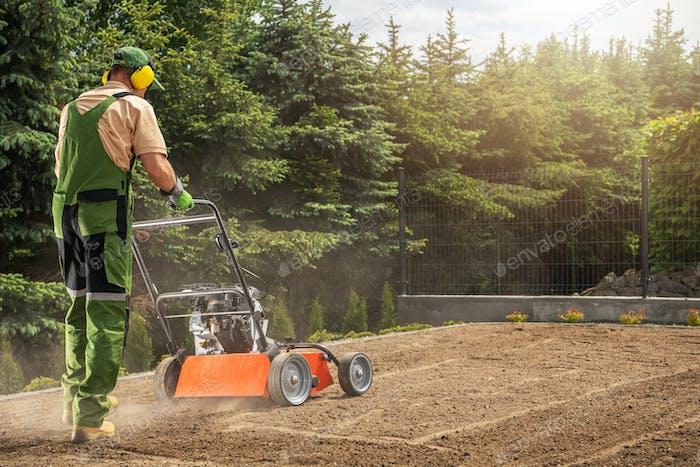Professional Gardener Aerating Backyard Lawn