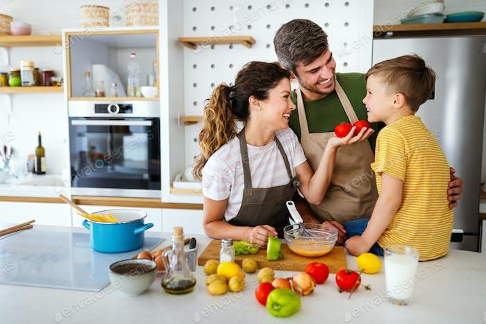 Glückliche Familie in der Küche, die Spaß hat und gemeinsam kocht
