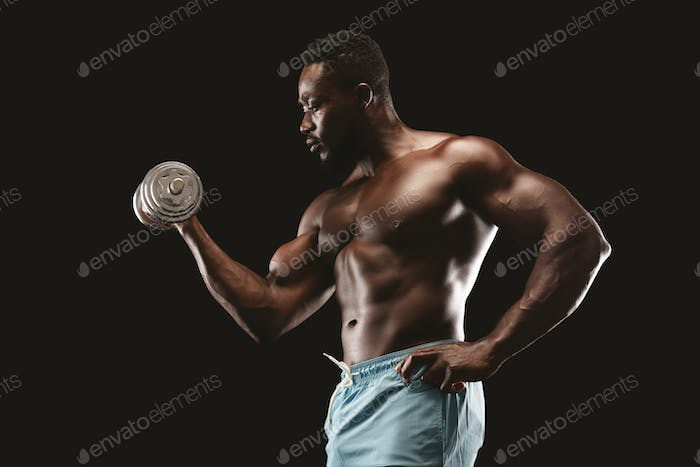 Side view of african bodybuilder doing single arm dumbbell curl