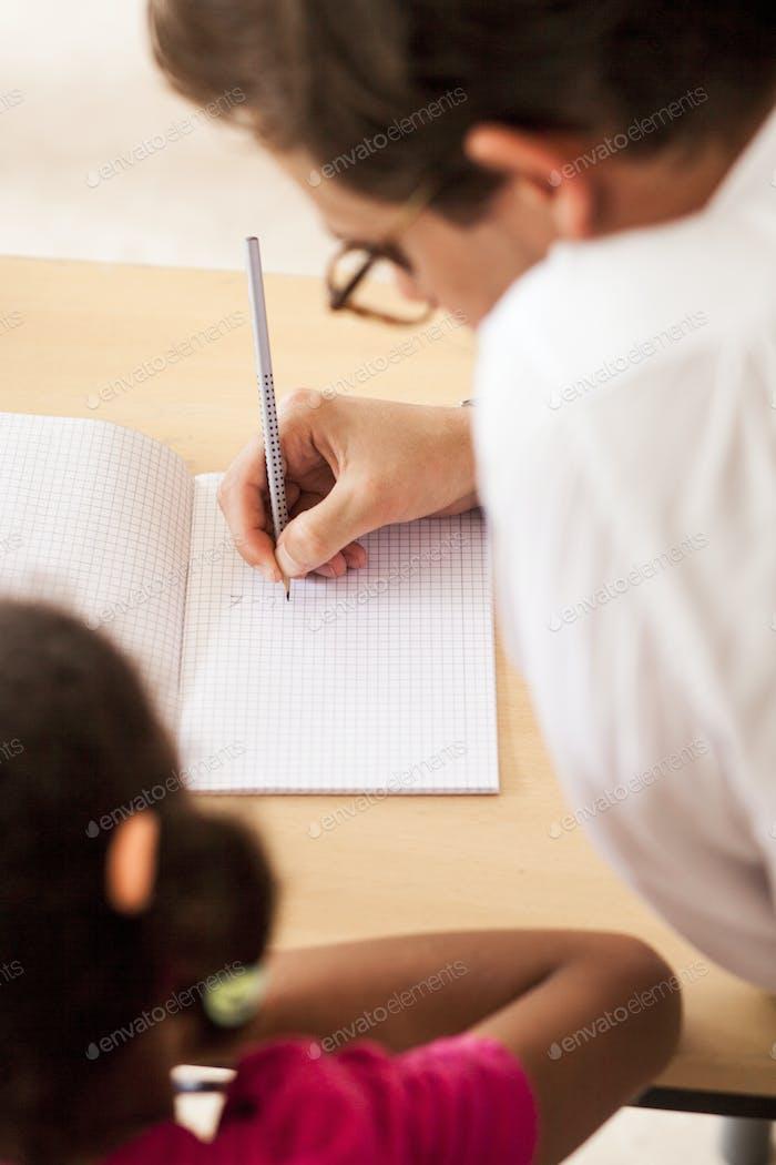 Male teacher teaching girl at desk