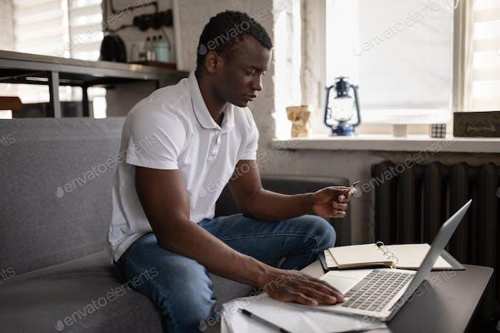 Schwarzer Mann machen Online-Bestellung auf Couch